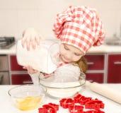 Glimlachend meisje met chef-kokhoed gezette bloem voor bakselkoekjes Stock Afbeeldingen