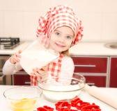 Glimlachend meisje met chef-kokhoed gezette bloem voor bakselkoekjes Stock Foto