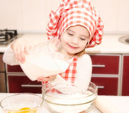 Glimlachend meisje met chef-kokhoed gezette bloem voor bakselkoekjes Stock Fotografie