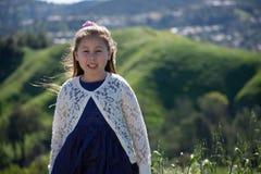Glimlachend Meisje met de Groene Achtergrond van het Heuvelplatteland royalty-vrije stock afbeelding