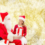 Glimlachend meisje met de Kerstman en giften Stock Afbeeldingen