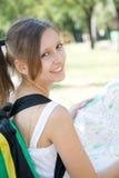 Glimlachend meisje met de stadskaart van de rugzakholding stock foto
