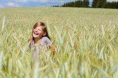 Glimlachend meisje met gesloten ogen op het gebied in stock foto