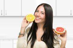 Glimlachend meisje met grapefruit Royalty-vrije Stock Afbeeldingen