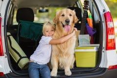 Glimlachend meisje met haar hond in autoboomstam Royalty-vrije Stock Foto