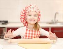 Glimlachend meisje met het rollende deeg van de chef-kokhoed Royalty-vrije Stock Foto's