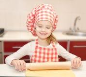 Glimlachend meisje met het rollende deeg van de chef-kokhoed Royalty-vrije Stock Fotografie