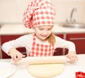 Glimlachend meisje met het rollende deeg van de chef-kokhoed Stock Fotografie