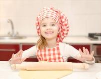 Glimlachend meisje met het rollende deeg van de chef-kokhoed Stock Afbeeldingen