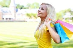 Glimlachend meisje met het winkelen zakken outdoors stock foto