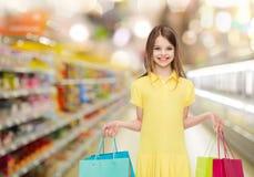 Glimlachend meisje met het winkelen zakken over supermarkt Royalty-vrije Stock Foto's