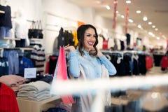 Glimlachend meisje met het winkelen zakken in winkel royalty-vrije stock afbeeldingen