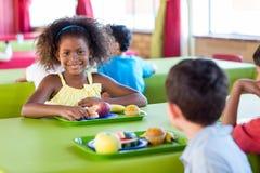 Glimlachend meisje met klasgenoten die maaltijd hebben royalty-vrije stock afbeeldingen
