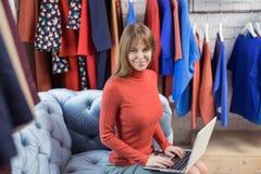 Glimlachend meisje met laptop in de opslag Stock Afbeeldingen