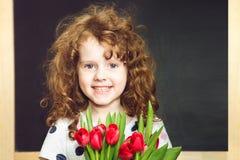 Glimlachend meisje met rode tulpen stock afbeeldingen