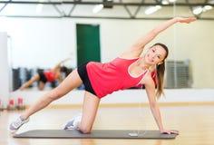 Glimlachend meisje met smartphone en oortelefoons in gymnastiek Royalty-vrije Stock Afbeeldingen