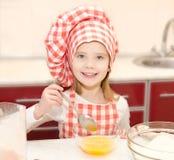 Glimlachend meisje met stirrring het koekjesdeeg van de chef-kokhoed Royalty-vrije Stock Foto