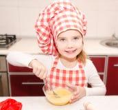 Glimlachend meisje met stirrring het koekjesdeeg van de chef-kokhoed Stock Foto's