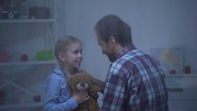 Glimlachend meisje met teddybeer die vader, achter terugkeren koesteren naar huis, regenachtige dag stock video