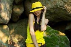 Glimlachend meisje met twee vlechten in een gele hoed royalty-vrije stock foto's