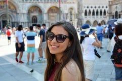 Glimlachend meisje met zonnebril, vrouwenmodel, in St Teken ` s Vierkant Venetië met toeristen en kerk op de bodem, de zomer van  royalty-vrije stock afbeeldingen