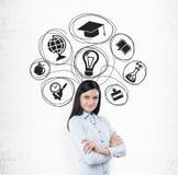 Glimlachend meisje met zwarte haar en onderwijspictogrammen Stock Foto