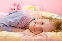 Glimlachend meisje op bed Royalty-vrije Stock Foto's