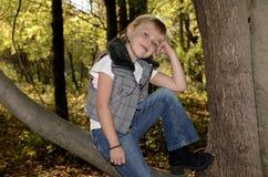 Glimlachend meisje op de tak van de de herfstboom Stock Foto's