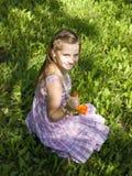 Glimlachend meisje op gras met een bloem Royalty-vrije Stock Afbeeldingen