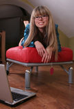 Glimlachend meisje op rode bank Stock Afbeelding
