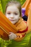 Glimlachend meisje in oranje hangmat in bos Stock Foto's