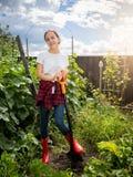 Glimlachend meisje in rubberlaarzen die schop houden en bij g werken Royalty-vrije Stock Foto