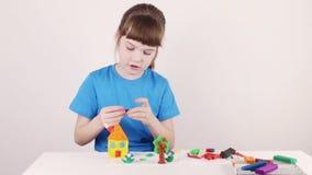 Glimlachend meisje in schimmelhuis van plasticine op witte lijst stock videobeelden