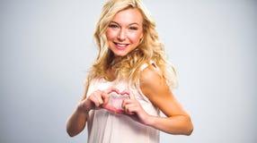 Glimlachend meisje in witte overhemden die hart met handen tonen Stock Foto
