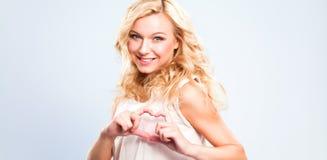 Glimlachend meisje in witte overhemden die hart met handen tonen stock fotografie