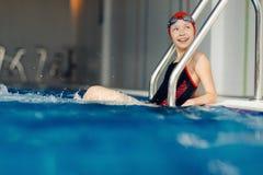 Glimlachend meisje in zwemmend kostuum in pool Stock Foto