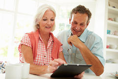 Glimlachend Midden Oud Paar die Digitale Tablet bekijken royalty-vrije stock afbeeldingen