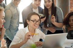 Glimlachend millennial professioneel team die samen met laptop werken stock fotografie