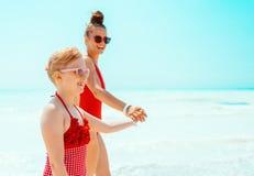 Glimlachend modern moeder en kind bij zeekust het lopen royalty-vrije stock fotografie