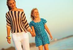 Glimlachend modern moeder en kind op zeekust in avond het lopen royalty-vrije stock foto