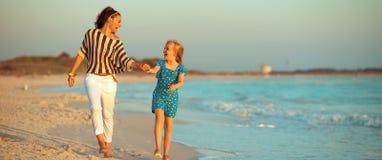 Glimlachend modern moeder en kind op zeekust bij zonsondergang het lopen stock afbeelding