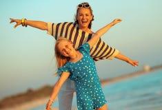 Glimlachend moeder en kind op zeekust in avond die prettijd heeft royalty-vrije stock afbeelding