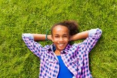 Glimlachend mooi Afrikaans meisje die op gras leggen Stock Afbeeldingen