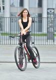 Glimlachend mooi jong meisje die zich met haar fiets op de straat bevinden De sc?ne van de stad stock afbeeldingen
