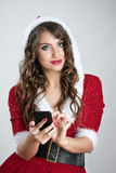 Glimlachend mooi Kerstmanmeisje in het rode hoodiekostuum typen op cellphone die camera bekijken royalty-vrije stock afbeeldingen
