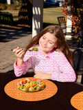 Glimlachend mooi meisje die gezonde fruitsalade in openlucht eten Stock Afbeeldingen