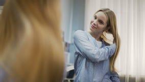 Glimlachend mooi wijfje die lang blond haar kammen dichtbij spiegel, haircare behandeling stock footage