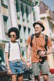 glimlachend multicultureel paar die van reizigers met camera en rugzakken handen van elk houden royalty-vrije stock afbeelding