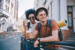 glimlachend multicultureel paar van toeristen die zich met beschikbare koppen bevinden van royalty-vrije stock afbeelding