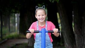Glimlachend, nam het gelukkige acht éénjarigenmeisje, doend oefeningen op openluchtoefeningsmateriaal, in openlucht, in het park, stock video